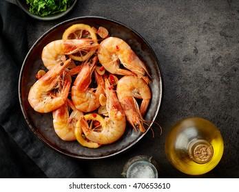 plate of fried prawns on dark table, top view