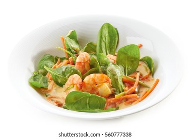 plate of fried prawns and vegetables with coconut sauce isolated on white background