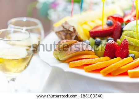 Plate with fruit and glass of champagne close-up