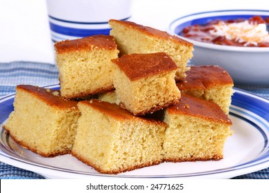Plate full of cornbread with chili in the background