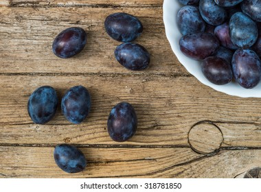 Plate full of fresh plums on a wooden background