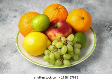 the plate full of fruits at the beton background, oranges and lime with lemon, green grapes and red apple at the plate - Shutterstock ID 1958437993