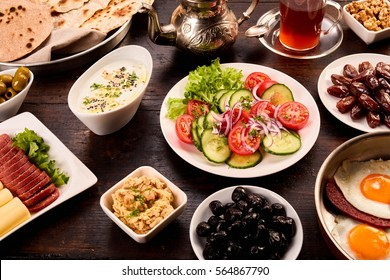 Plate full of oriental breakfast. Dark background plate with different assorted breakfast ingredients and components in a 45 degrees view for arabic food concepts.