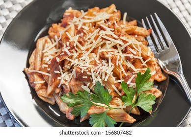 A plate full of Penne A La Vodka is topped with parmesan cheese and fresh parsley.