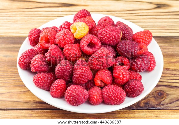 Plate full of ripe raspberries on rustic wooden table