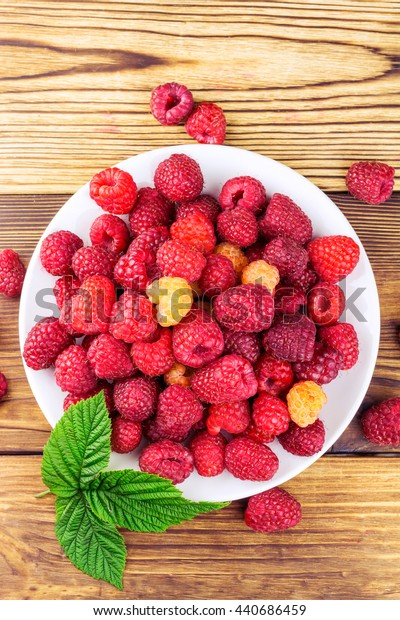 Plate full of ripe raspberries on rustic wooden table, top view