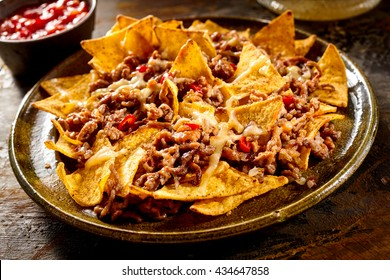 Plate full of yellow corn nachos and cooked ground beef with bowl of red salsa in background over wooden table