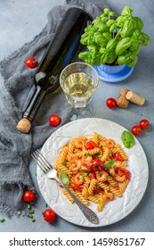 Plate of fusilli pasta with tomato sauce, cherry tomatoes, shrimps, a glass of homemade white wine and a vase with green basil on a textured grey table. Top view.