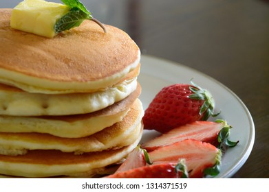 a plate of gluten free pancake accompanied with fresh strawberries
