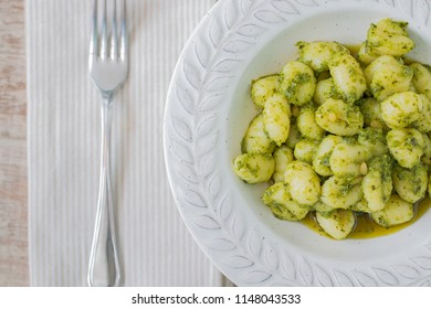 A plate with gnocchi with basil pesto and a fork.