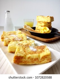 A plate of golden brown french toast with icing sugar
