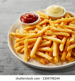 Plate of golden French fries, potato chips, or Pommes Frites served with little bowls of tomato sauce and mayonnaise in a close up view, square format