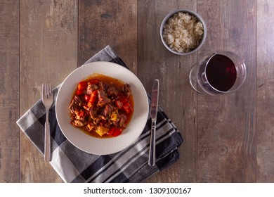 A plate with goulash or beef stew on the table. Photographed in a flat top down view.