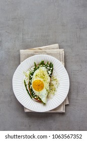 Plate of green aspargus, fried egg, feta cheese and micro greens spring sandwich over light concrete background. Healthy eating, slimming, diet lifestyle concept. Flat lay, top view