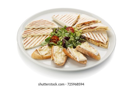 a plate of grilled cheese. Toast with camembert cheese. quesadilla with cheese and bacon. White background
