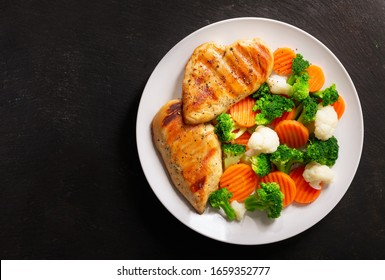 plate of grilled chicken with vegetables on a dark background, top view