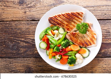 plate of grilled chicken with vegetables on wooden table, top view