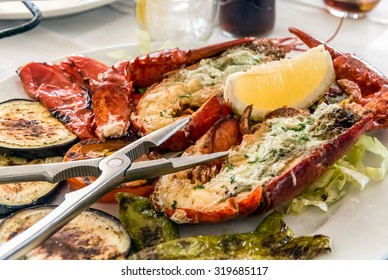 Plate with grilled lobster on the sliced vegetables and lemon in the center.