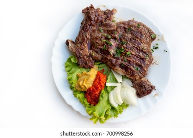 Plate of grilled ribs with traditional Croatian side dish of ajvar