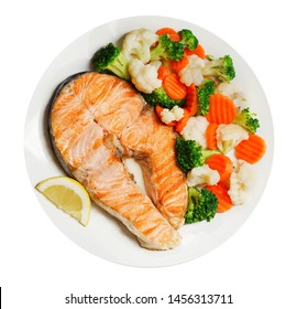 plate of grilled salmon steak with vegetables isolated on white background, top view