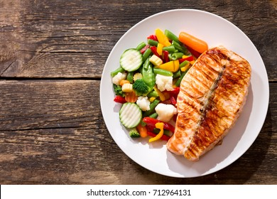 plate of grilled salmon steak with vegetables on wooden table, top view