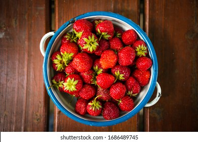 Plate with group of ripe, delicious strawberry on a brown wooden table. Top view.