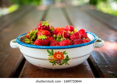 Plate with group of ripe, delicious strawberry on a brown wooden table. Selective focus