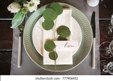 plate with a guest card signed by hand with caliber ink. Decoration of a table for a festive dinner.