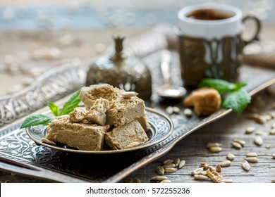 Plate with halva from sunflower seeds and Turkish coffee on a bronze tray, selective focus.