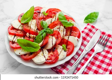 Plate of healthy classic delicious caprese salad with ripe tomatoes and mozzarella cheese with fresh basil leaves on white marble background. Italian cuisine concept.