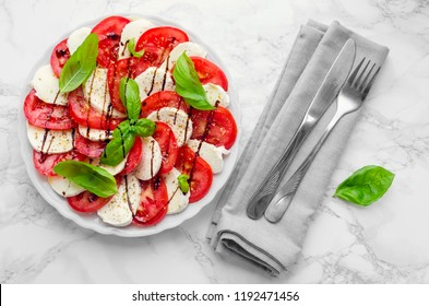 Plate of healthy classic delicious caprese salad with ripe tomatoes and mozzarella cheese with fresh basil leaves on white marble background. Italian cuisine concept. Top view.