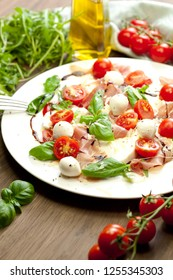 Plate of healthy classic delicious caprese salad with ripe tomatoes and mozzarella cheese with fresh basil leaves on white wooden background