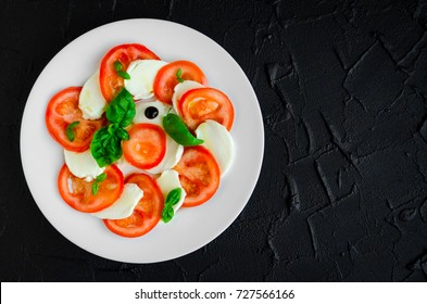 Plate of healthy classic delicious caprese salad with ripe tomatoes and mozzarella cheese with fresh basil leaves on dark concrete background with space for text. Italian food. Top view. Copy space.