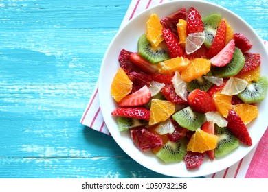 Plate of healthy fresh fruit salad on wooden background. Top view.