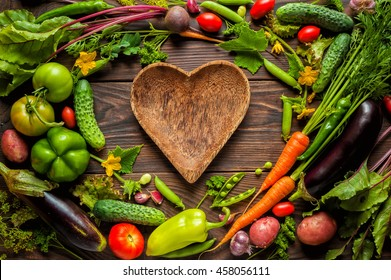Plate heart shape surrounded with Fresh organic Vegetables on Wooden Background. Healthy Vegetarian food, View from above.