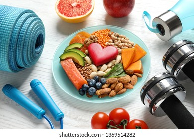 Plate with heart-healthy products and sports equipment on wooden background