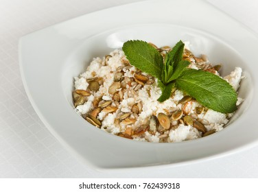 plate of homemade curd with pumpkin seeds on white background