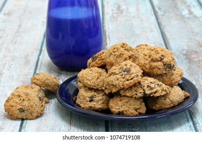A plate of homemade, fresh baked raisin oatmeal cookies on a rustic blue table.