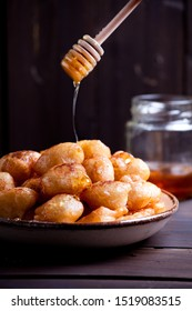 Plate of homemade greek donuts loukoumades with honey and cinnamon
