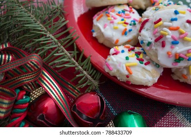 A plate of homemade holiday cookies with white icing and colorful sprinkles on a red plate with pine branches, bells and ribbon accent pieces.