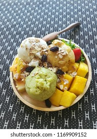 A plate of homemade ice cream from fresh fruits of coconut passion fruit and avocado are put on top of lettuce and decorated with raisin muesli cherry tomatoes and fresh mango, give the beautiful look