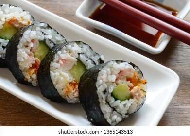 a plate of homemade maki sushi roll accompanied with soy sauce