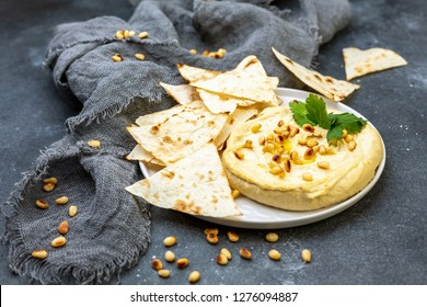 Plate of homemade traditional hummus, pieces of toasted homemade pita bread and pine nuts on a textured dark table, selective focus.