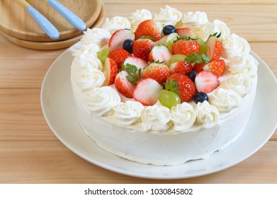 a plate of homemade vanilla cheesecake with whipped cream frosting and topped with strawberries, grapes and blueberries