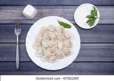 plate of hot meat dumplings with sour cream on the table, top view still life