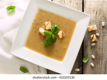 Plate of hot thick beans soup in white plate over wood grunge background
