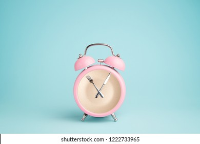 Plate inside the pink alarm clock. Concept of intermittent fasting, lunchtime, diet and weight loss