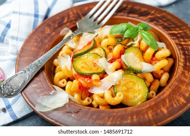 Plate with Italian pasta cavatappi with zucchini tomatoes, parmesan cheese and basil close up on a textured dark background, selective focus.
