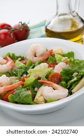 Plate of Italian shrimp salad with shrimp, tomatoes, artishocke hearts, Romane lettuce leaves, fava beans, and pine nuts. Olive oil.