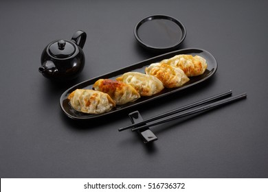A plate of Japanese gyoza over black background